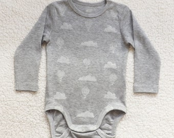 100% organic cotton bodysuit with balloons and clouds. Hand printed