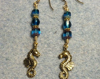 Gold seahorse charm dangle earrings adorned with turquoise Czech glass beads.