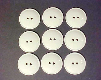 Nine winter white or light ivory plastic 2- hole buttons