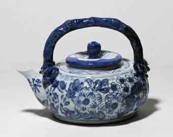 Round vintage blue and white Asian floral ceramic teapot, decoration,