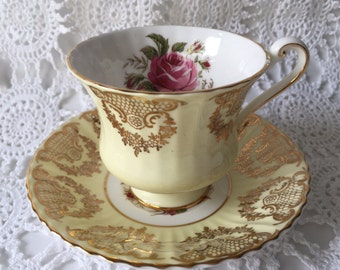 Beautiful ParagonTeacup Ornate Gold Filigree Pattern On Pale Yellow Background. Pretty Pink Rose. Fine Bone China England.Condition: Nice sh