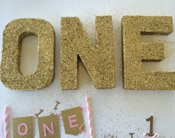 "Gold glitter first birthday "" one "" letters"