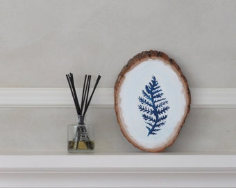 Acrylic painted log with blue and white fern design on both sides