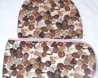 Assorted Chocolates on pink Tea cosy and ovengloves