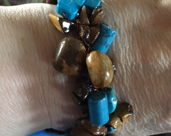 17 brown beads and turquoise colored glass beads on copper wire