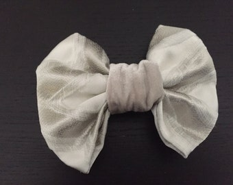 unique one of a kind, handmade patterned hair bow on a clip. Shades of cream and silvers
