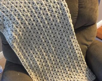 Chunky crocheted cream colored throw