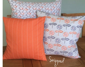 Orange and grey cushions in a bright and modern fresh design.