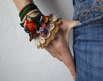 crochet cuff with beaded flowers in cream, brown, pink, red, blue and green colors