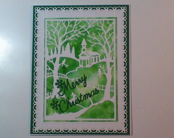 Christmas card with church,trees, birds and fence in green and white.
