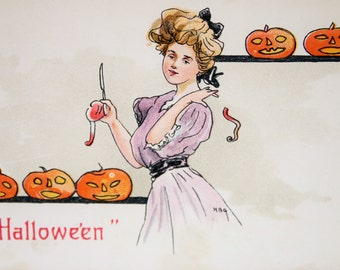 Vintage Halloween Postcard of a lady carving an apple surrounded by Jack o' Lanterns Artist Signed HGB #2215