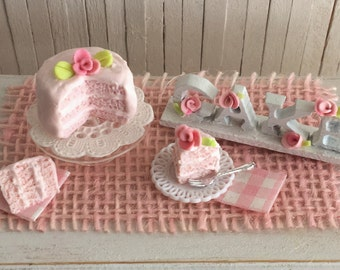 """Miniature Pink Layer Cake With A Rose, A Glass Cake Stand, A Slice Of Cake, And A """"Cake"""" Sign In White Wood Letters With Tiny Pink Roses"""