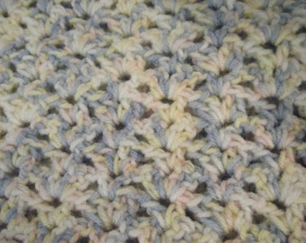 Crocheted baby blanket in pastel pink, blue and yellow