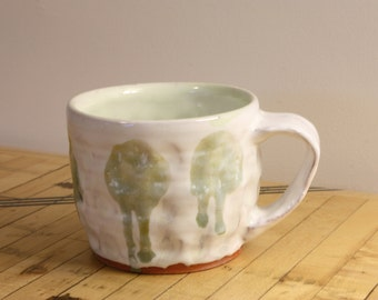 White and light green ceramic cup