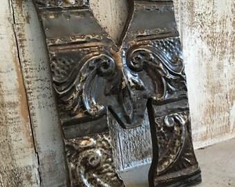 "Patchwork letter ""M"" designed with antique tin ceiling tile"
