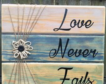 Love Never Fails reclaimed wood sign