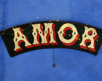 Hand-painted, luminous 'AMOR' wall sign in Victorian lettering