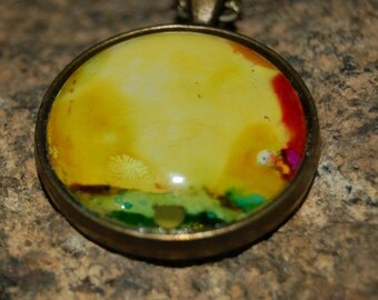 Hand painted alcohol ink abstract in yellow and green with rainbow highlights set in brass circle with domed glass and chain. 02-11