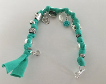 Charms on turquoise fabric bracelet