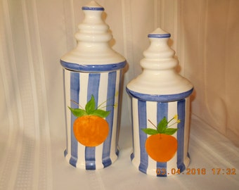 A pair of counter top containers. blue and white striped with oranges on the side.