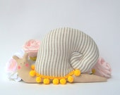 Snail toy, stuffed Snail animal  toy in modern decorative style. Grey white striped fabric, yellow pompom trim. Toy and home decor, gift
