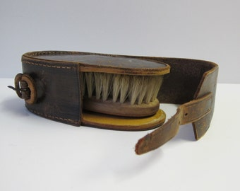 Vintage wooden clothes brush in oval leather case.