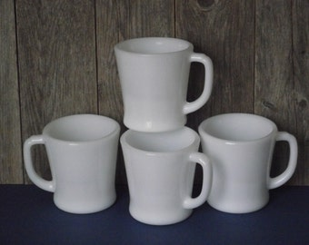 """Four white milk glass Fire King """"D"""" handled thick glass 8 ounce coffee mugs, manufactured by Anchor Hocking, likely in the 1960's"""
