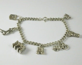 "Silver charm bracelet & seven charms vintage dated 1979 8"" long 26.1 grams st"