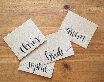Hand lettered wedding place cards on brown kraft card