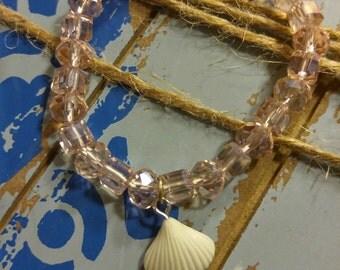 Whisper pink multi-shape faceted glass beaded stretch bracelet w/white seashell charm