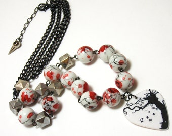 Guitar Pick Necklace - Black and white tree design pick with red and black splattered white glass beads and pyramid stud metal beads