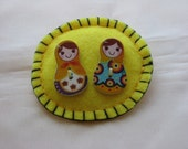 Embroided Brooch/Pin with wood figures of two russian dolls on yellow felted background