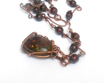 Copper steampunk wire wrapped necklace with brown color transparent resin pendant and brown glass beads.