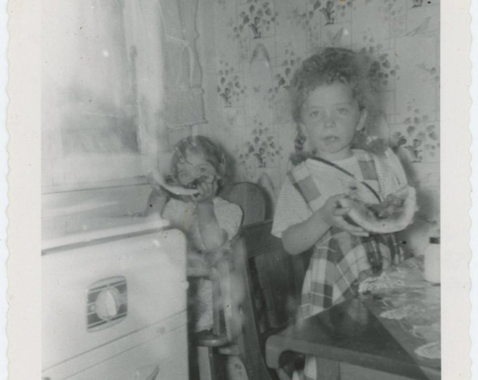 Two Small Girls Eating Watermelon in Kitchen, c1950s Vintage Snapshot Photo (67481)