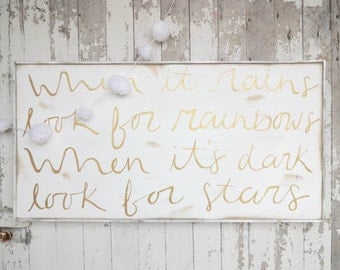 When it rains look for rainbows gold and white rustic wood sign