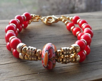 Women's 2 strand bracelet with red beads, gold discs and lampwork center with lobster clasp