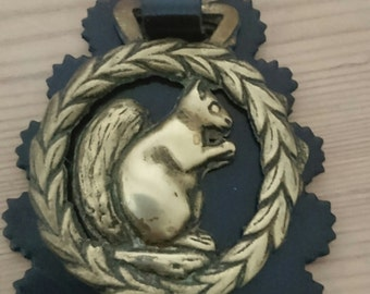 Vintage squirrel horse brass on a leather strap