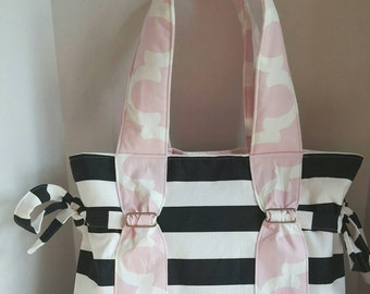 Baby girl Diaper bag, large, black and white stripe with pink quatrefoil straps and lining. Front slip pocket and option of zipper top.
