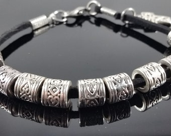 Black leather bracelet with pewter beads and a cross charm.