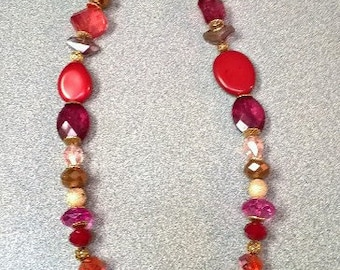 Beautiful glass and stone beaded necklace with cranberry colors.