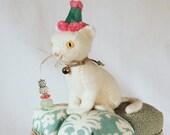 White Wool Kitty Pincushion on a vintage barkcloth and damask tuffet