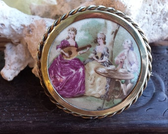 Vintage Victorian hand painted brooch of Victorian ladies and gentlemen