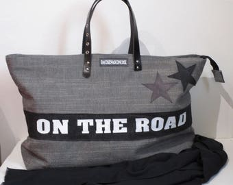 Gray travel bag with leather handles and lettering