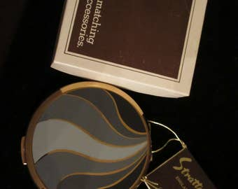 Gorgeous Multi Hue Gray on gold swirl design loose powder compact by Stratton of England. Vintage but never used. In original box with tag.