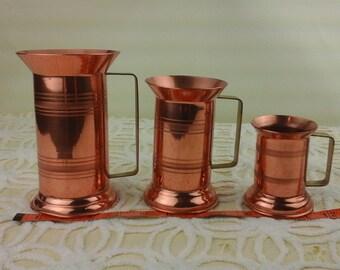 Vintage set of three copper mugs.