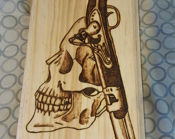 Skull and gun wood plaque