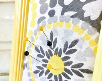 framed table top pin cushion with patterned fabric. Wood frame is bright yellow and patterned fabric gray and yellow by Farm Fancy Love.