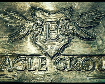 Handmade embossed sign that reads: 'Eagle Group' with two eagles and a shield in the middle of them. Made from a monster energy drink can.