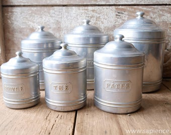 Complete set of six French brocante metal canisters by Tournus-Uni