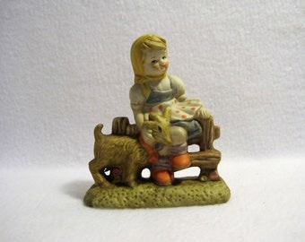 Ceramic figurine Young girl sitting on a fence, petting a goat.